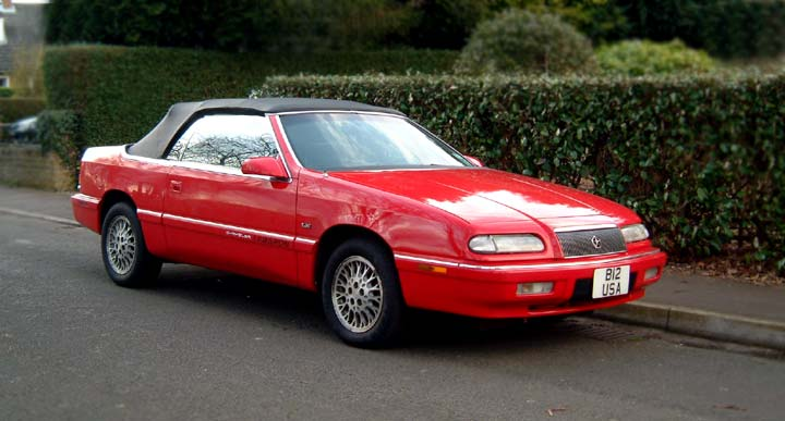 A 1995 cherry red, black top, Chrysler Lebaron convertible