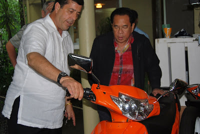 Dave Dewbre explaining the Chavit how to operate the electric, and extremely energy efficient motor bike.