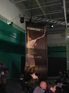 Karim Darwish sits beneath one of the large banners during his 3rd/4th place play-off against Amr Shabana