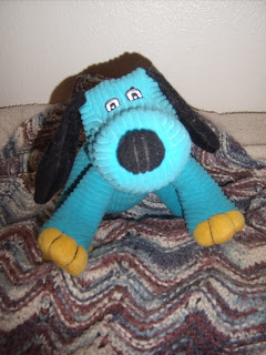 A blue stuffed dog with a black nose and ears and yellow feet. He's made out of a corduroy type material