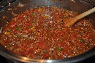 a big pot of spaghetti sauce, its bright red and you can see tomatoes, onions, green and yellow bell pepper pieces, meat and tons of seasonings