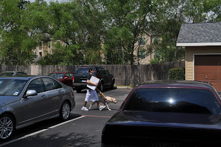 Darrell walking down the parking lot with a big white box in his hand and Egypt's harness in the other - dog included of course, this shot is from the patio of our apartment right as Darrell is walking between two cars