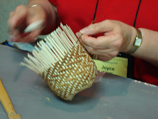 Joyce works on an elm bark and Black ash basket in Alice Ogden's class.