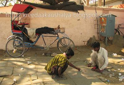 Boys engrossed in the same game beside their idle cycle rickshaws
