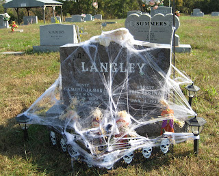 This is a tombstone decorated with spider webbing and other Halloween stuff