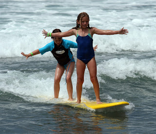 After these two campers learned to surf at Aloha Beach Camp, they shared a board and learned tandem surfing, too!