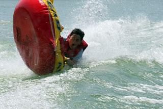 A camper flips his tube at Aloha Beach Camp Summer Camp at Castaic Lake, California