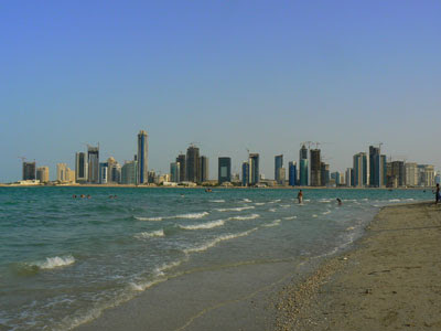 The Doha skyline is visible from the beach