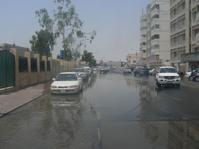 Cars navigate a flood in Al Nasser Street