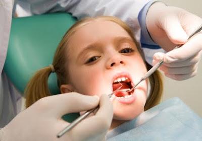 A dentist checks a little girl's teeth.