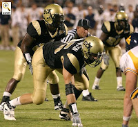 Three defensive University of Central Florida football players on the natural turf of a night football game preparing for the ball to be snapped.