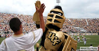 A male fan in a t-shirt high fives the UCF golden knight mascot near the field at a crowded outdoor football game.