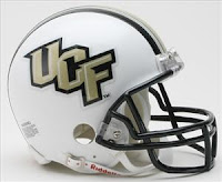 A large white UCF helmet with gold lettering, a black face mask and a gray background.