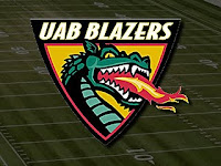Yellow, red, black, and green triangular shaped UAB Blazers logo with fire breathing dragon is set against the backdrop of a green computerized football grid iron.