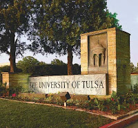 Sun shines on a marble sign reading The University of Tulsa centered by bricks with green grass and green leafy trees around the monument.