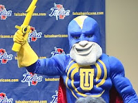 Superhero looking mascot wears a muscular blue outfit with a red cape and a yellow lighting bolt.