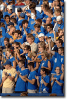 Young fans in blue tshirts clap during an event.