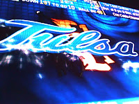 Blue computer graphic reading Tulsa in light blue against a black and blue background.