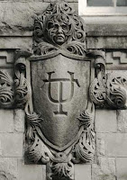 Close up view of a concrete decorative piece of art with a shield with the letters U and T overlapping.
