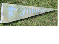 Tattered triangle shaped pennant flag with worn blue calligraphy font reading Tulane and similar colored image of a football player carrying a ball.  The pennant is laid on green grass.