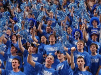 A sea of University of Memphis fans in blue t-shirts in the stands at a basketball game waiving blue poms.