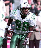 Wide receiver Randy Moss carrying a football in a green and white Marshall University uniform.