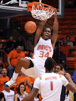 A basketball player slam dunks in a white uniform that reads Miners in orange letters while yelling during a game.