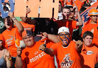 Six fans in orange UTEP t-shirts cheer and yell at a game.