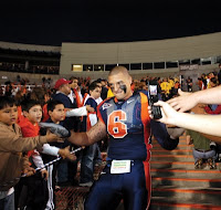 Football player in blue and orange uniform high fives fans in a stadium at night with his helmet off.