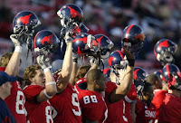 SMU football players hold up black helmets with red mustangs.