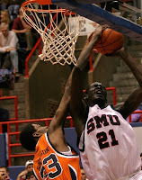 Basketball player in white uniform with blue writing reading SMU #21 takes the ball to the basket against a defender in an orange uniform.