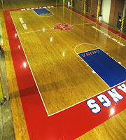 basketball court with red border and blue free throw lanes. Red baseline reads Mustangs in white letters.