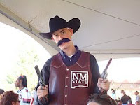 New Mexico State University cowboy mascot with pistols and cowboy hat.