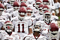 New Mexico State football players in red helmets and white uniforms.