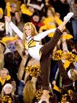 Wyoming cheerleader holds leg above her head at football game.