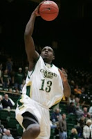 CSU basketball player in white uniform goes up for a dunk.