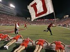 University of Utah cheerleaders do push ups while man with Utah flag runs on football field.