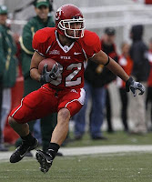 Utah football player carries the ball in a red uniform in a game.