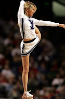 BYU cheerleader in white uniform holds leg back over her head while standing.