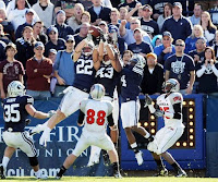 BYU wide receivers go up for a good catch in front of onlooking fans.