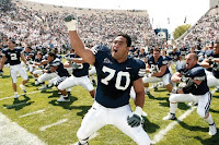 Large BYU offensive lineman cheers on crowd at a football game on a sunny day.