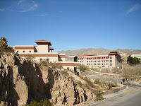 Light brown rocks form a wall on the side of a road winding around two large four story Spanish architecture buildings.