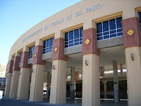 Brown columns with glass panes on a circular building with white letters reading The University of Texas at El Paso.