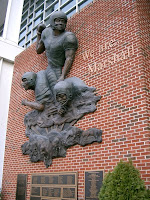 We are Marshall red brick wall memorial of three bronzed football players.