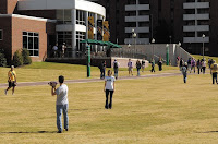 students on a grass lawn walk to class in front of a brick student center.