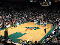 Fans fill a basketball arena with a green dragon breathing fire design drawn on the center of the court.