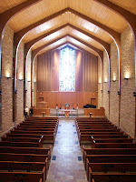 Interior view of large wooden chapter from the rear with rows of pews on each side of the empty chapel.
