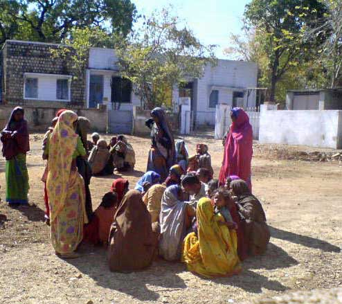 women sitting crouched in saris
