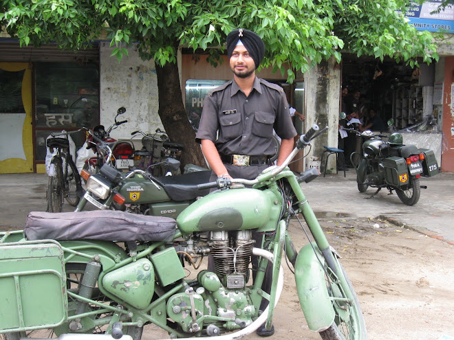 Indian Soldier poses with his Royal Enfield.