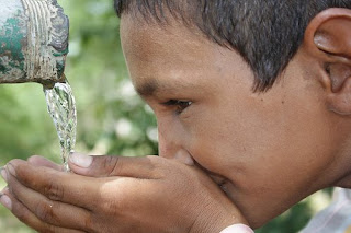 A school boy from Tilonia drinks from a tap from a rainwater harvesting tank that provides clean drinking water for the school children. The rainwater harvesting system collects rainwater from the roof of the school. It is filtered and stored for drinking in this semi-arid region of Rajasthan, India.